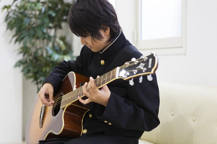 楽器を弾く高校生